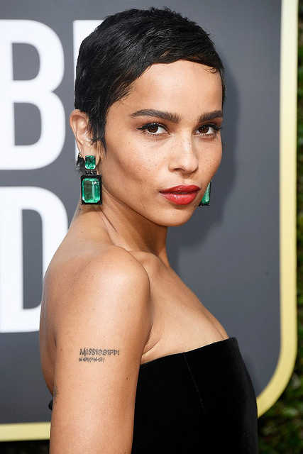 Zoe Kravitz wearing mega-bold emerald cut emerald earrings. The earrings are by Lorraine Schwartz and the emeralds total 130 carats and are set in black jade